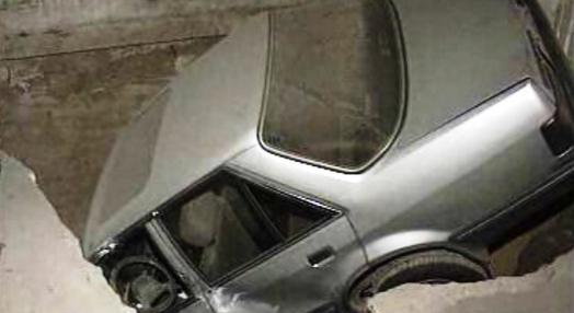 Carro cai em buraco no interior de uma garagem