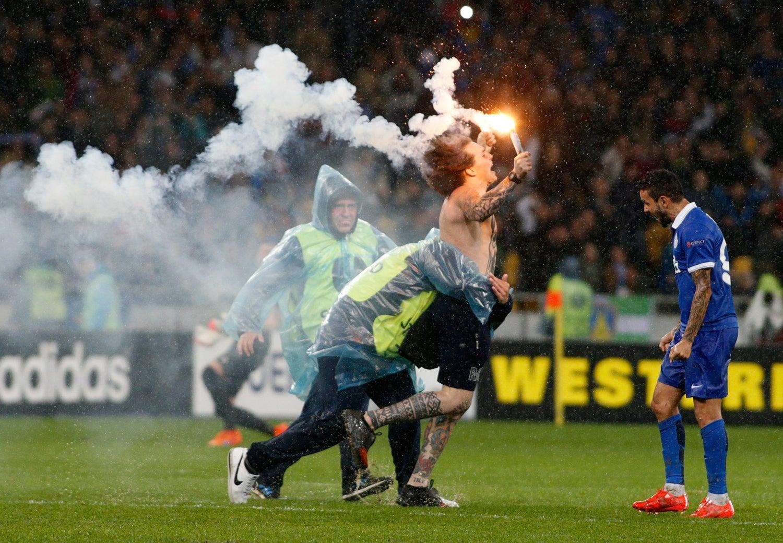 O segurança tenta impedir que o adepto do Dnipro Dnipropetrovsk entre em campo para comemorar a vitória sobre o Napoli na semi-final da Liga Europeia em Kiev - 2015 /Valentyn Ogirenko - Reuters
