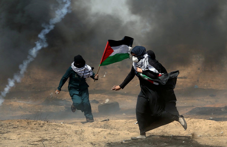 Manifestantes palestinianos fogem do gás lacrimogéneo /Ibraheem Abu Mustafa - Reuters