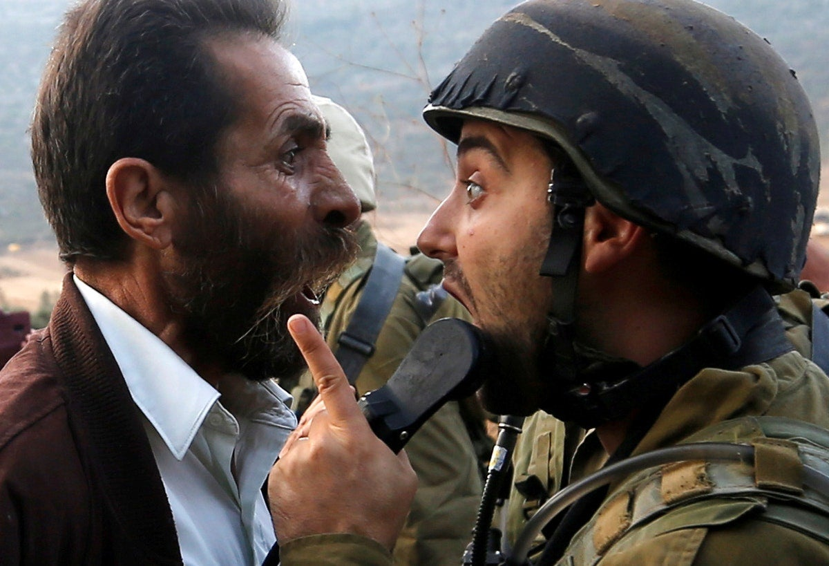 Um palestiniano discute com um soldado israelita /Mohamad Torokman - Reuters