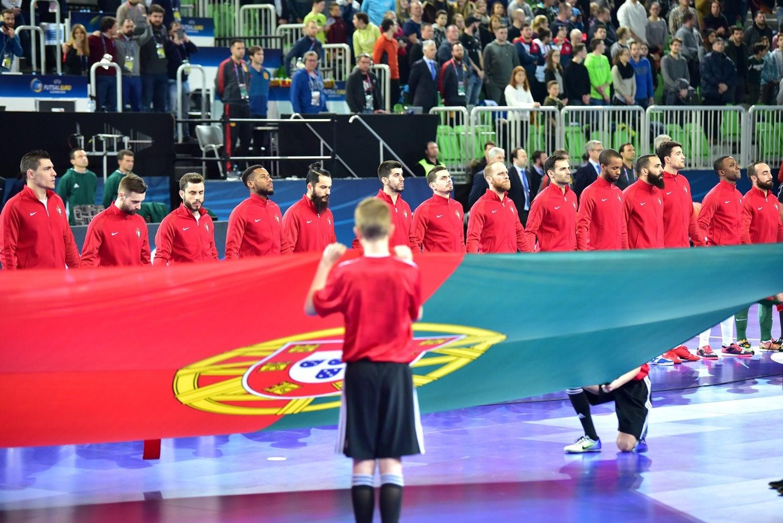 Os jogadores dão as mãos até ao embate final. A bandeira mostra o caminho. (Foto: Igor Kupljenik - EPA)
