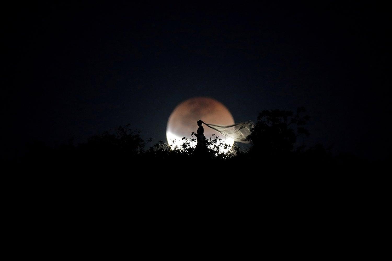 Uma noiva posa durante eclipse lunar /Ueslei Marcelino - Reuters