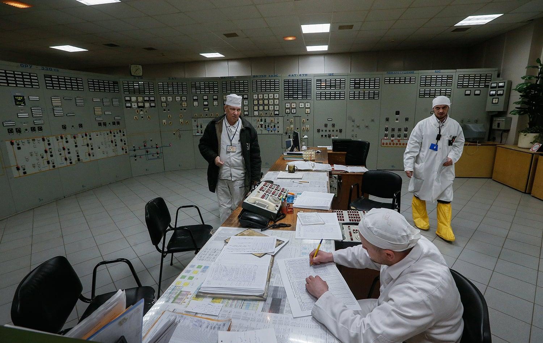 Operadores verificam os dispositivos na sala de controlo no primeiro reator de Chernobyl / Sergey Dolzhenko - EPA