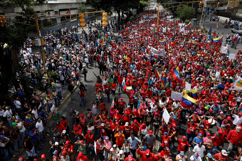 Os apoiantes (de vermelho) do Presidente da venezuelano Nicolas Maduro marcham frente aos apoiantes da oposição / Carlos Garcia Rawlins - Reuters