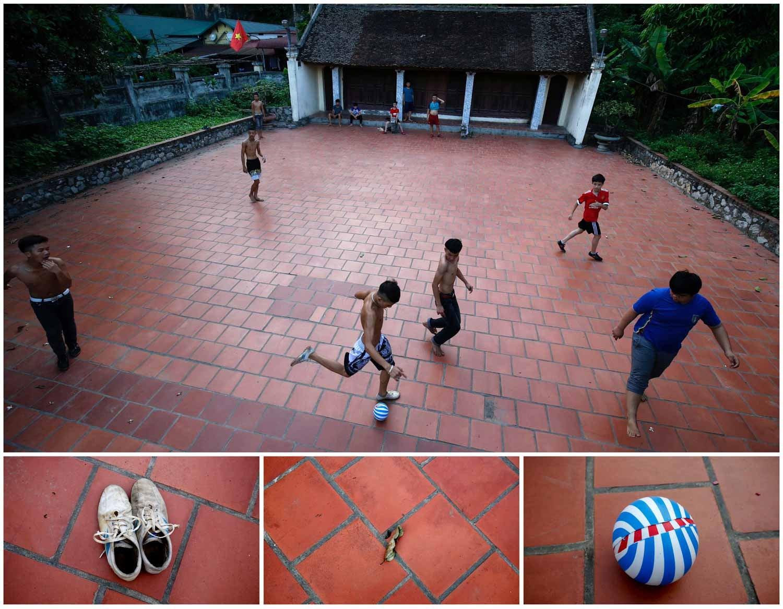 Na cidade de Hanói, capital do Vietname, um grupo de crianças joga uma partida de futebol em frente a um templo na aldeia de Hoang Xa. Foto: Nguyen Huy Kham - Reuters