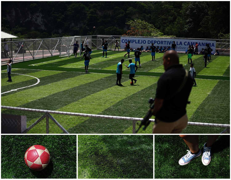Na cidade de Soyapango, em El Salvador, várias crianças jogam futebol antes da inauguração de um novo complexo desportivo. Do lado de fora das grades do campo vê-se um homem a segurar uma arma. Foto: Jose Cabezas - Reuters