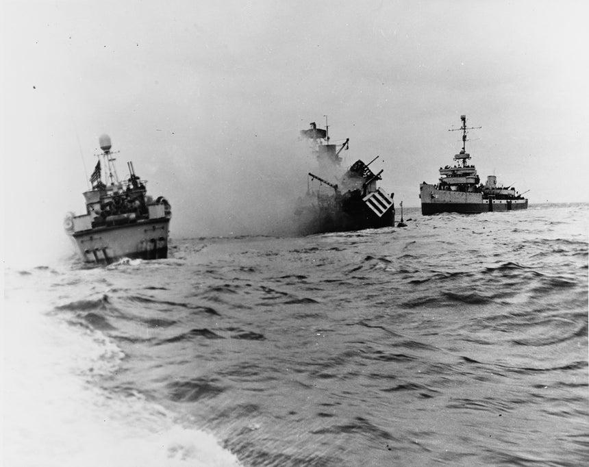 O draga-minas USS Tide afunda após chocar contra uma mina submarina e é assistido pelo  contratorpedeiro PT-509 (esq.) e também pelo draga-minas USS Pheasant (dir.) /Reuters