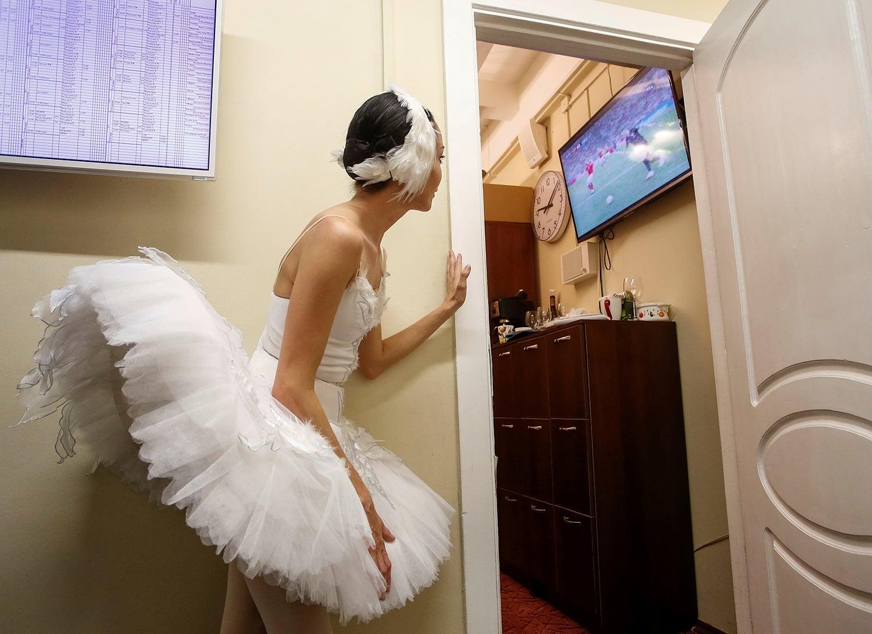 Uma bailarina aproveita para espreitar o jogo entre a Rússia e a Croácia durante o Mundial de Futebol /Anton Vaganov - Reuters