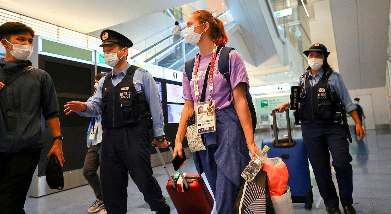 A atleta bielorrussa Krystsina Tsimanouskaya escoltada pelas autoridades japonesas no aeroporto, aquando o seu pedido de asilo.   Foto: Issei Kato - Reuters