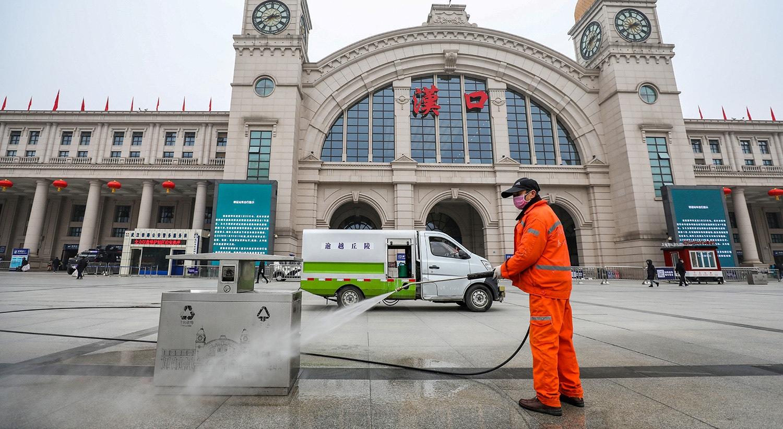 Um trabalhador higieniza a praça em frente a uma estação ferroviária em Wuhan |  China Daily via Reuters