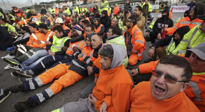 Os estivadores sentaram-se no chão e tentaram impedir que a polícia assegurasse a passagem do autocarro com trabalhadores substitutos