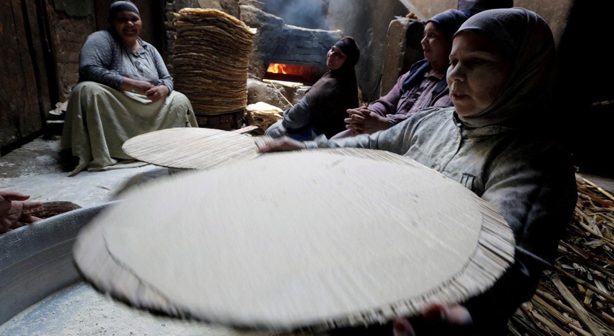 Egipto. Em Beni Suef, mulheres muçulmanas confecionam o pão tradicional para venderem durante o Ramadão | Hayam Adel - Reuters
