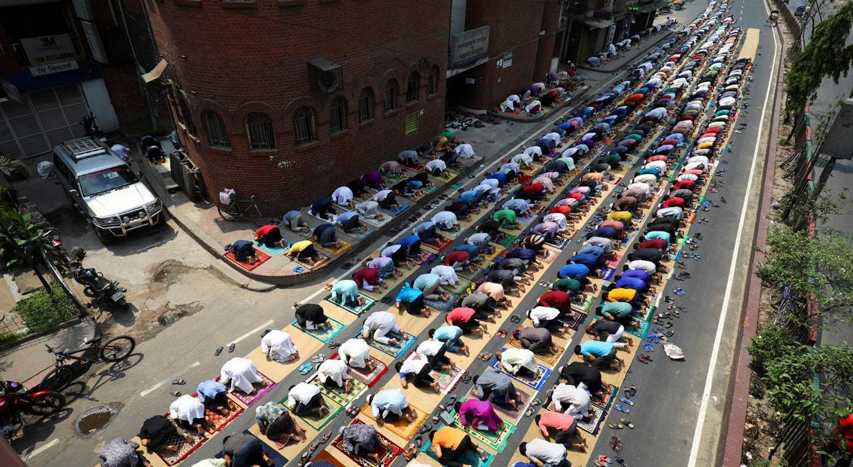 Bangladeche. Na cidade de Dhaka, os crentes rezam em frente à mesquita | Mohammad Ponir Hossain - Reuters