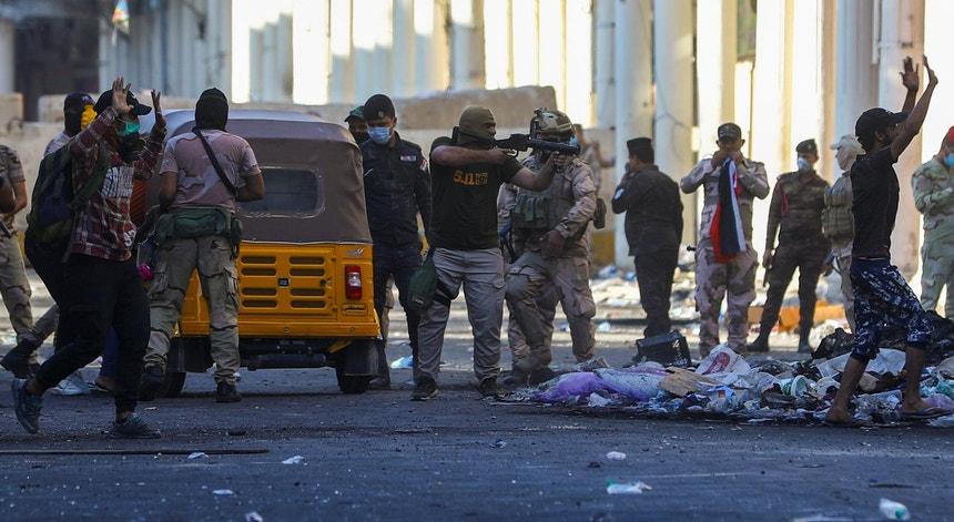 Um polícia aponta a sua arma diretamente contra um manifestante, durante as manifestações de sexta-feira 8 de novembro em Bagdade, Iraque
