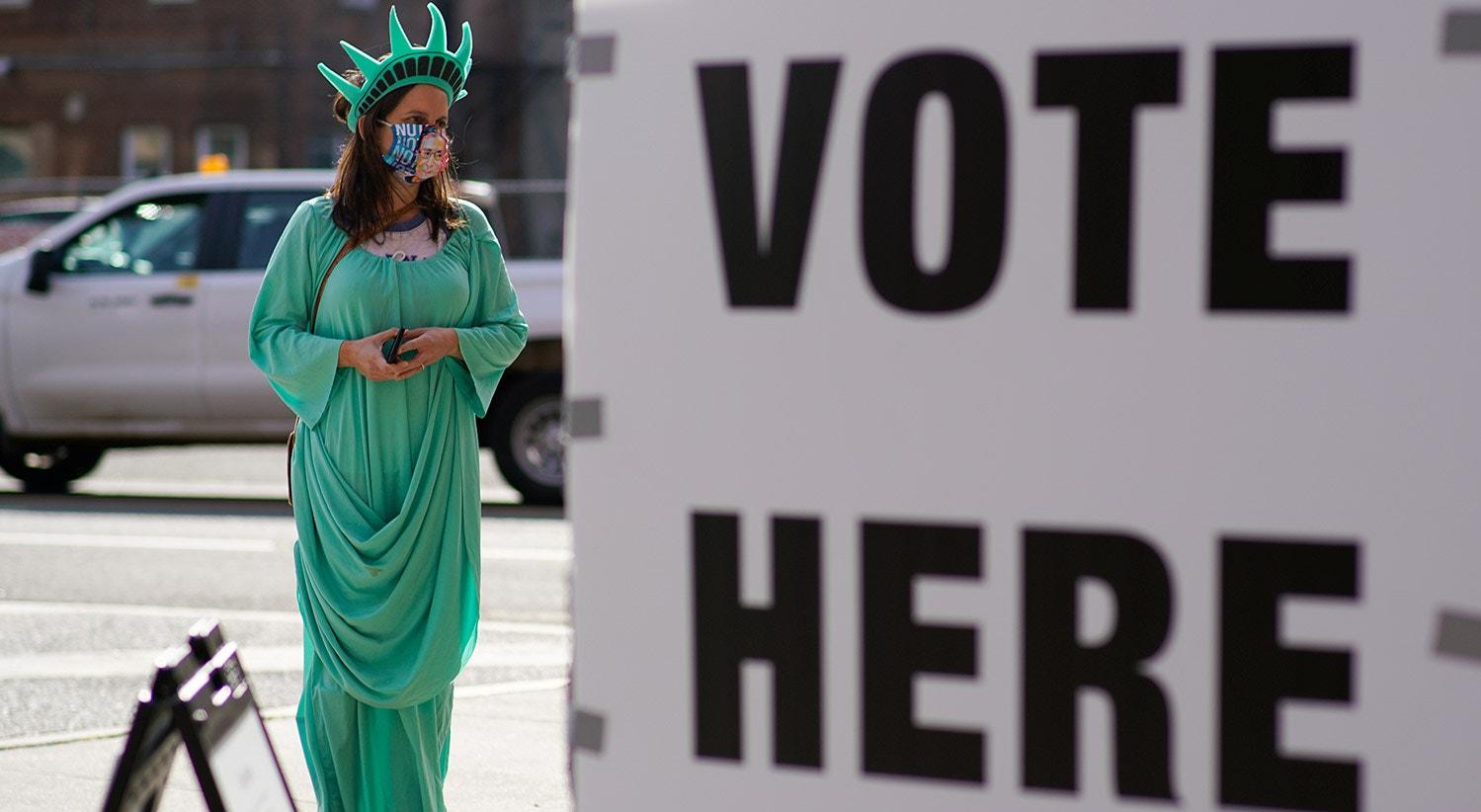 Uma mulher vestida de Estátua da Liberdade está perto de um local de votação no dia das eleições em Hoboken, Nova Jersey | REUTERS/Eduardo Munoz