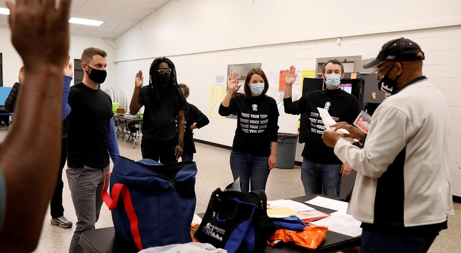 Os membros das mesas de voto prestam juramento na secção eleitoral do Condado de Fulton durante as eleições em Atlanta, Geórgia | REUTERS/Chris Aluka Berry