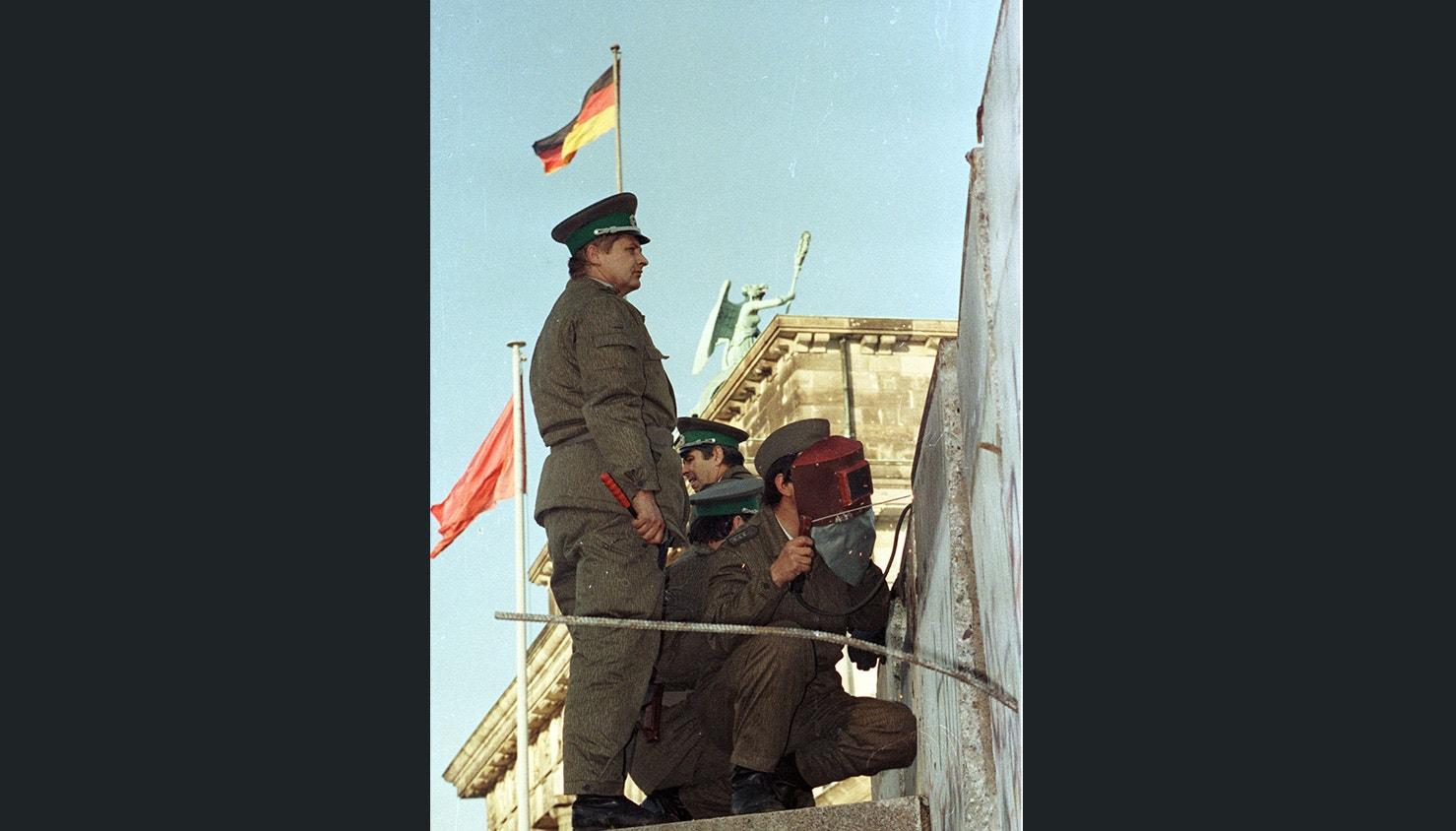 Guardas da fronteira reparam uma secção do muro destruída no dia anterior. 11 de novembro de 1989 | Reuters
