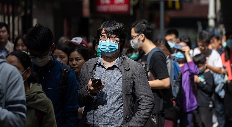 Fila de pessoas para obter suplementos de vitamina C e frascos de desinfetante para as mãos em Hong Kong | Jerome Favre - EPA