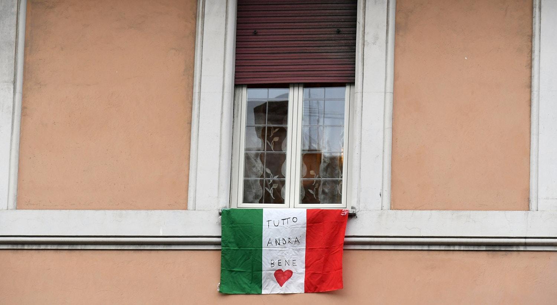 """A bandeira italiana diz: Tudo irá correr bem, """"Tutto andra bene"""", uma frase que se tornou num símbolo de esperança em Itália por causa da pandemia do novo coronavírus. / Alberto Lingria - Reuters"""