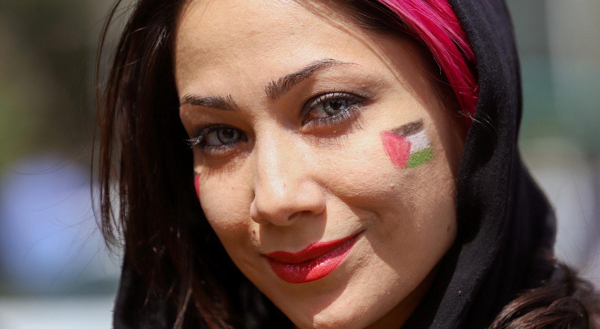 Irão. Mulher iraniana com a bandeira palestiniana pintada no rosto, demonstrando solidariedade, na marcha anual que assinala o Dia de Jerusalém | Majid Asgaripour/WANA - Reuters