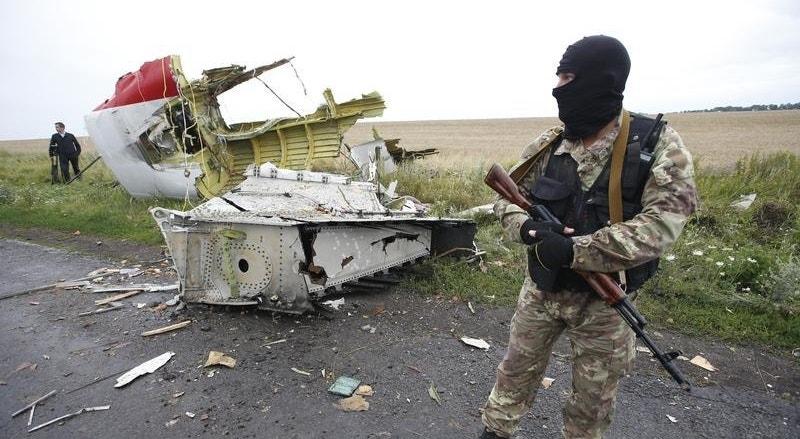 Militante separatista russo guarda pedaços do aparelho da Malaisia Airlines abatido em julho de 2014 nos céus da Ucrânia