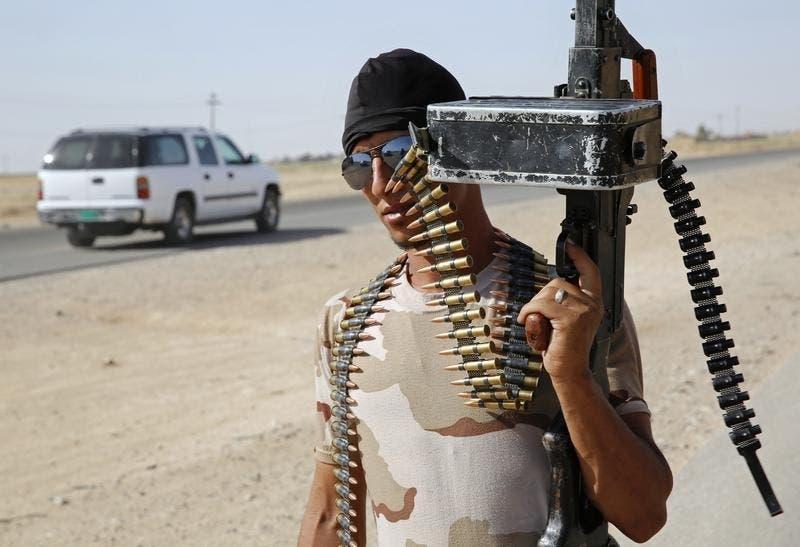 Combatente das Brigadas Badr, xiitas iraquianas, mostra a sua arma num posto de controlo no norte do Iraque Foto: Reuters
