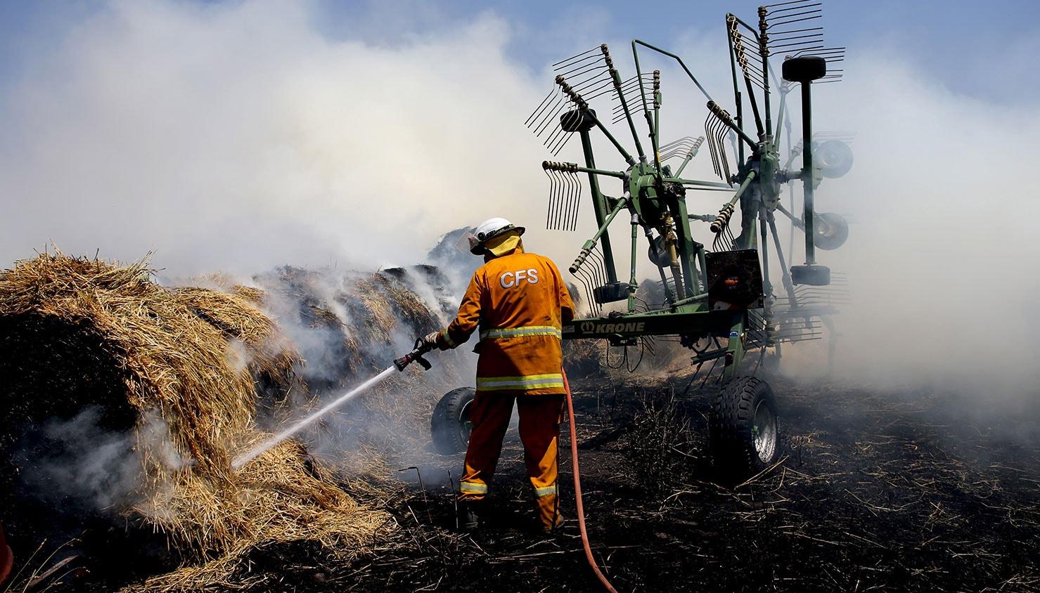Bombeiro coloca fardos de feno em chamas para combater o incêncio em Adelaide Hills, Austrália | Kelly Barnes - EPA