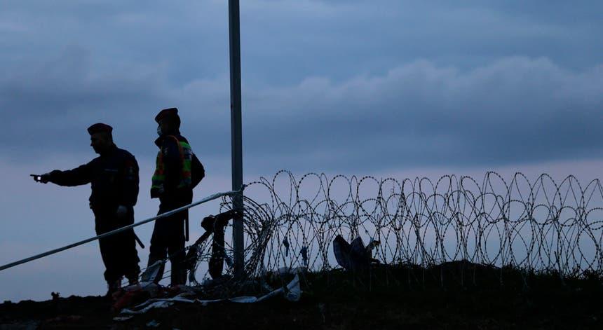 Guardas fronteiriços húngaros de vigilância a migrantes que aguardam vez de passar a fronteira em Botovo, Croácia, a 16 de outubro de 2015. A Hungria anunciou o encerramento das suas fronteiras com a Croácia a partir das 00h00 de sábado, dia 17.