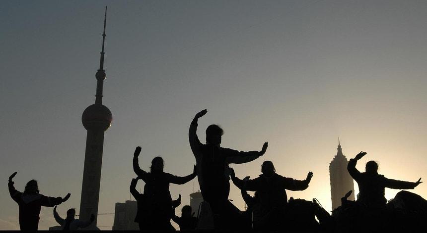 Um grupo de pessoas pratica a dança de boxe de Mulan em Xangai, China, em 2006