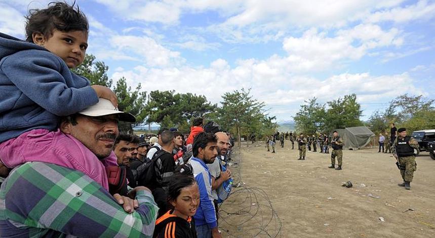 Polícia da Macedónia dia 21 de agosto de 2015, de guarda junto a uma barreira fronteiriça de arame onde se encostam centenas de migrantes vindos do Médio Oriente e que pretendem chegar à Europa central.