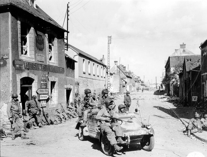 Paraqueditas da 101ª Divisão Aerotransportada com um carro alemão em Carentan /Reuters