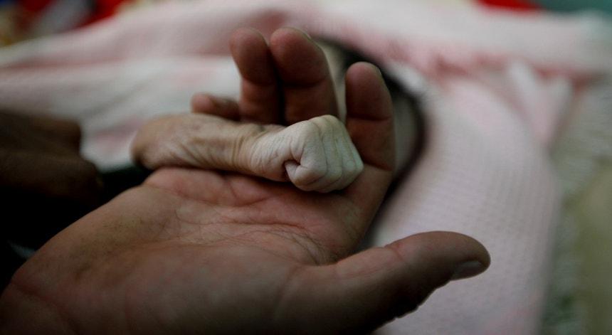 Pai segura a mão de bebé que morreu à fome, no Iémen