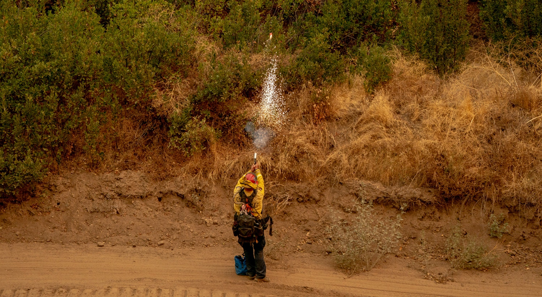 Um bombeiro dispara um foguete para controlar a intensidade do Fogo El Dorado ao queimar uma encosta perto de Yucaipa na Floresta Nacional de San Bernardino, Califórnia. |Kyle Grillot /EPA