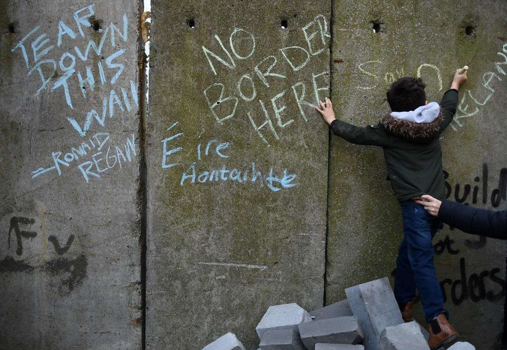 Um rapaz escreve uma mensagem num muro de fronteira durante um protesto de militantes anti-Brexit, Borders Against Brexit em Carrickcarnan, Irlanda, 26 de janeiro de 2019. REUTERS/Clodagh Kilcoyne