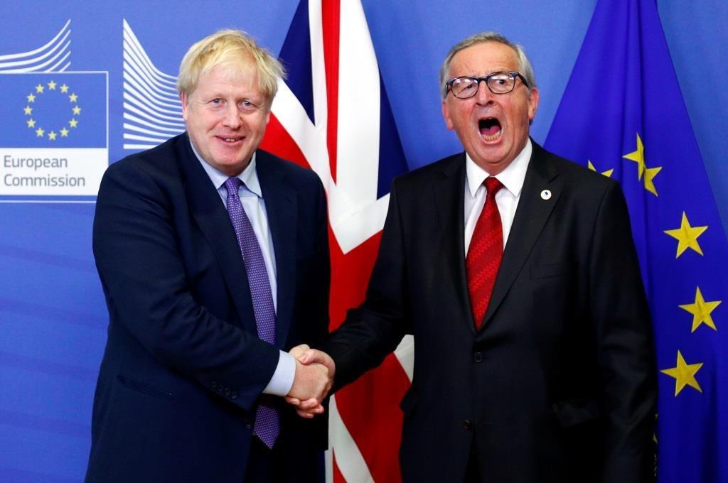 O Presidente da Comissão Europeia, Jean-Claude Juncker, e o Primeiro-Ministro Boris Johnson apertam as mãos durante uma conferência de imprensa depois de chegarem a acordo sobre o Brexit. Este acordo foi realizado á margem da cimeira dos líderes da União Europeia, em Bruxelas. 17 Outubro 2019. REUTERS/Francois Lenoir