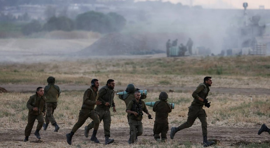 Soldados israelitas carregam ogivas de artilharia num campo próximo à fronteira entre Israel e a Faixa de Gaza