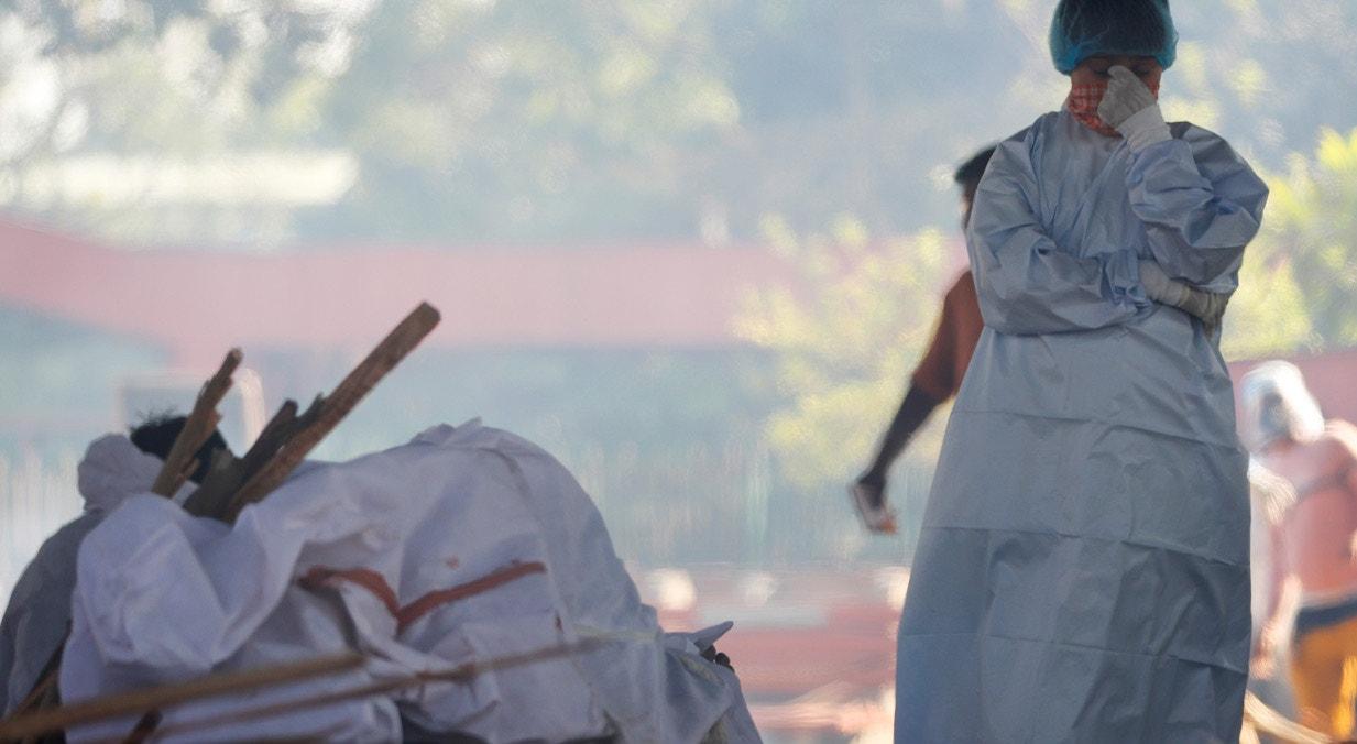 Nova Deli. Rapaz chora junto do corpo do pai que irá ser cremado | Adnan Abidi - Reuters