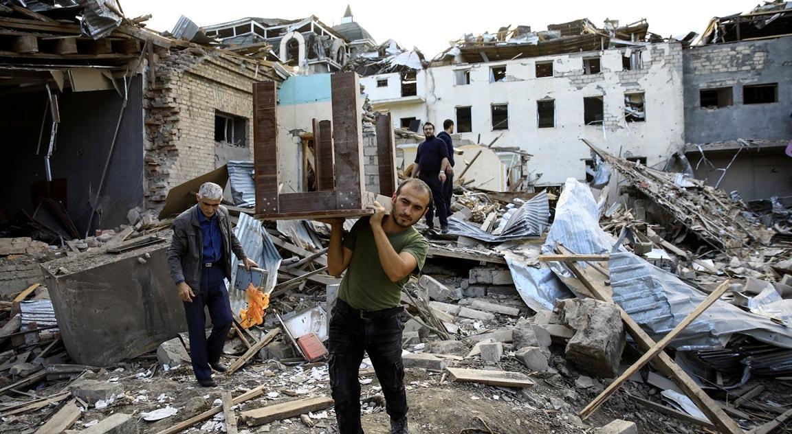 Cidade de Ganja, morador recolhe mesa de destroços, pós-bombardeamento   Umit Bektas - Reuters