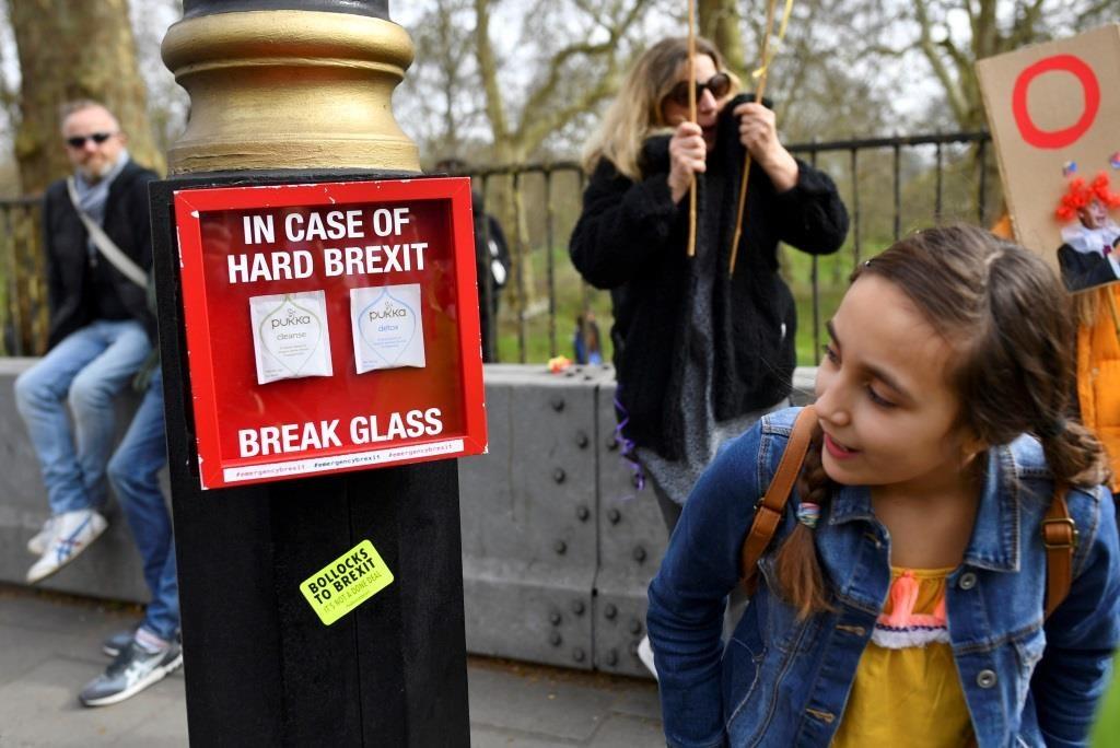 """Uma criança olha alegremente e de forma curiosa para uma caixa pendurada num poste contendo duas saquetas de chã e que diz: """"No caso de um Brexit dificil, quebrar vidro"""". Londres, 23 março 2019. REUTERS/Dylan Martinez"""