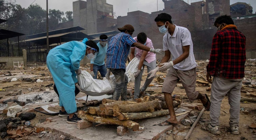 Pranav Mishra é ajudado pelos familiares na cremação da mãe que morreu vítima de Covid-19