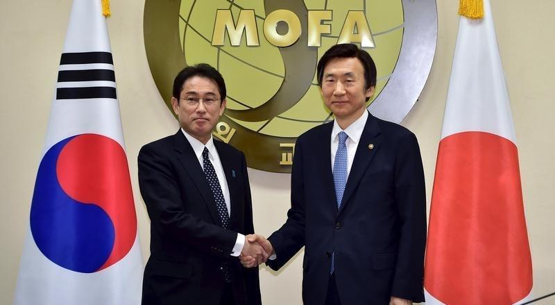 Aperto de mão entre os ministros dos Negócios Estrangeiros do Japão e Coreia do Sul, depois da reunião em Seul