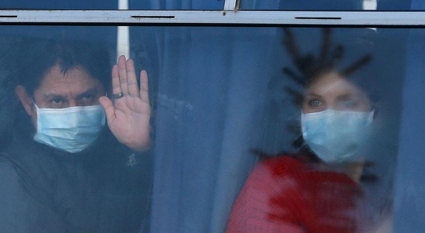 Dois passageiros vindos da China, possivelmente infetados com o COVID-19, espreitam pela janela do autocarro dia 20 de fevereiro de 2020, em Kharkiv, Ucrânia, a caminho do local de quarentena.