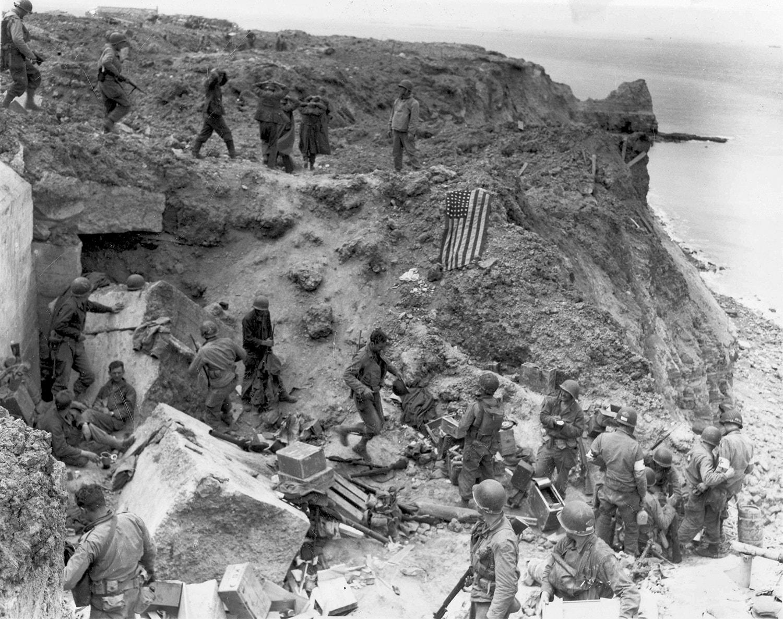 Tropas americanas e prisioneiros junto a um bunker alemão destruído na praia de Juno /Reuters