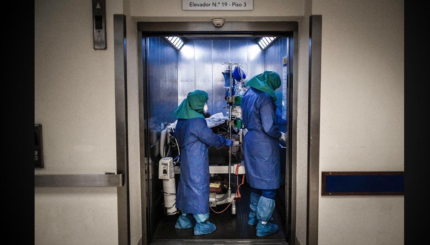 Enfermeiros no interior de um elevador de acesso à Unidade de cuidados intensivos dos doentes com Covid-19. / Mário Cruz - Lusa