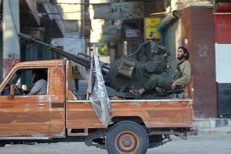 Um militante do grupo rival do Estado Islâmico, Frente al-Nusra, numa carrinha que transporta uma arma anti-aérea em Ariha, Síria Foto: Reuters