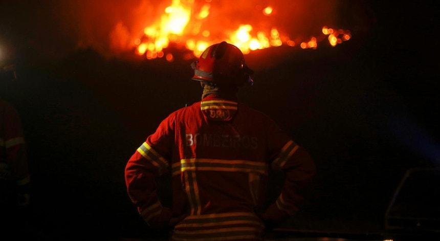 Desde junho que os incêndios não dão descanso aos bombeiros. Na foto, um operacional olha as chamas en Góis, a 19 de junho de 2017