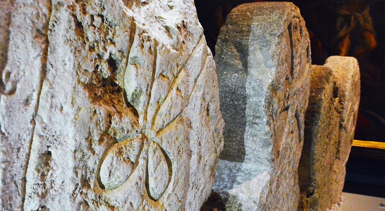 Cabeceira de sepultura. Séc XIV. Destaca-se a representação de uma tesoura e agulha, indicadores da profissão do defunto