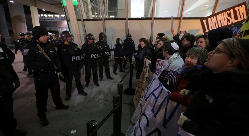 Manifestantes concentram-se diante do terminal 4 do aeroporto JFK, em Nova Iorque, sob o olhar da polícia de choque