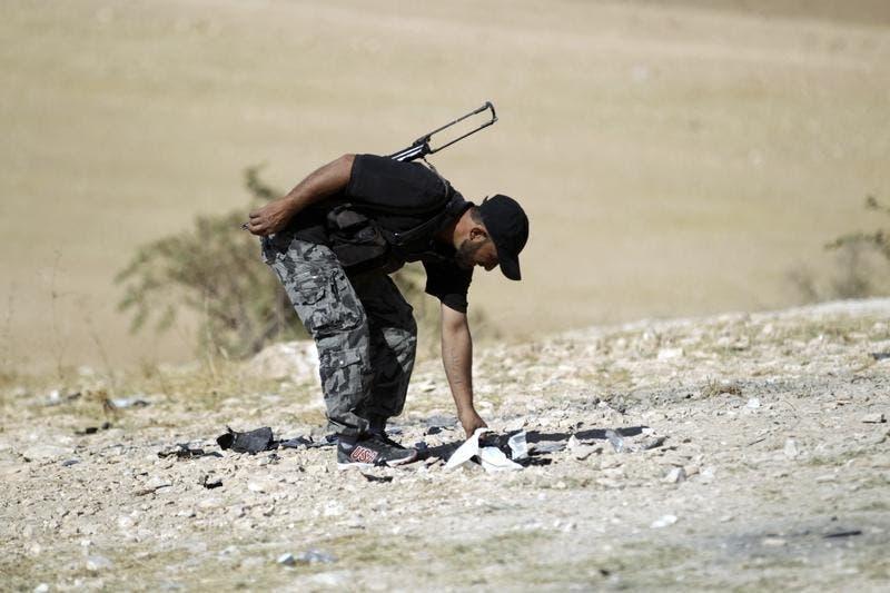 Um rebelde sírio apanha pedaços de um drone, de um grupo de cinco, armadilhados com explosivos e lançados contra uma base do grupo em Idlib Síria. Os destroços do drone poderão ser reutilizados para fazer bombas. Foto: Reuters
