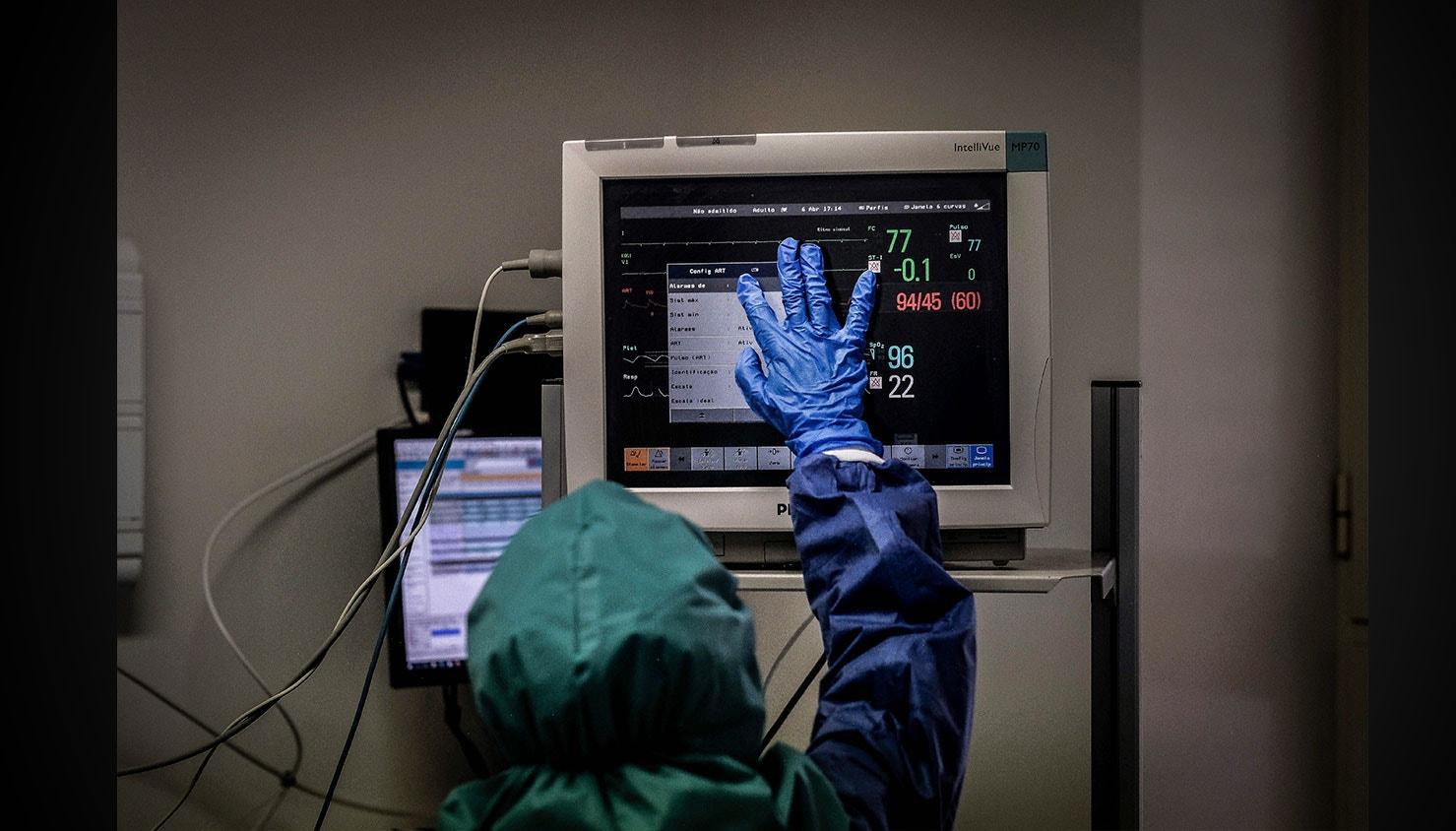 Um enfermeiro coloca a mão no ecrã onde são observados os sinais vitais de um doente ventilado na Unidade de cuidados intensivos dos doentes com Covid-19. / Mário Cruz - Lusa